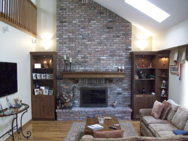 Wall Sconces over Lighted Custom Cabinetry with Corner Curio, Custom Mantel with Hand Carved Corbells, Custom Color Glass Doors and Matching Log Holder with Tool Set, Rebricked Hearth Extention.