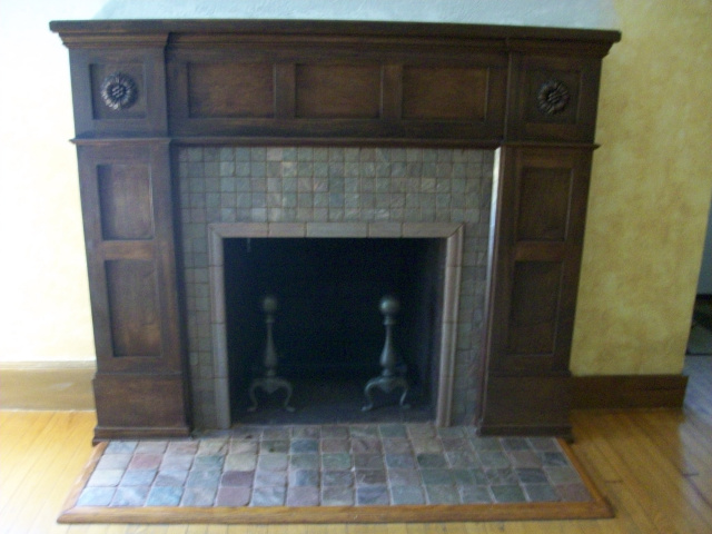A Custom Arts & Crafts Mantel in hand rubbed English Chestnut with Arts & Crafts Stone Tile Surround and Hearth are complimented by the restored Andirons.