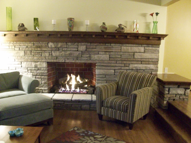 A 15 Foot Custom Arts & Crafts Mantel in hand rubbed English Chestnut with Matching Table Top, Stone Cleaning, Firebox Firebrick Panels, Variable Flame Gas Log Set and New Hearth Stones.
