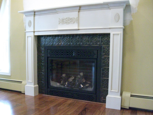 A new gas firebox with ornamental grills, realistic logs and glowing fire, surrounded by hand painted artisan tins, wrapped in a beautiul custom designed period mantel in mayonase color with a light tea glaze.