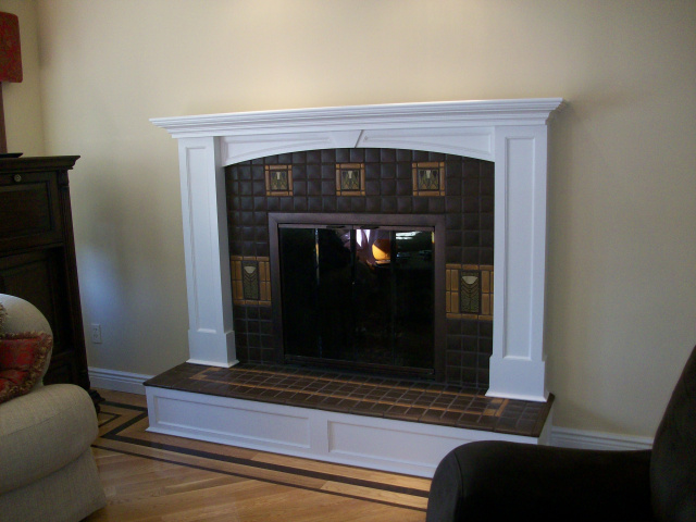 Custom hand made Motawi tile surround with bordered flower features and hearth extention design. Custom finished arched woodwork mantel and riser.