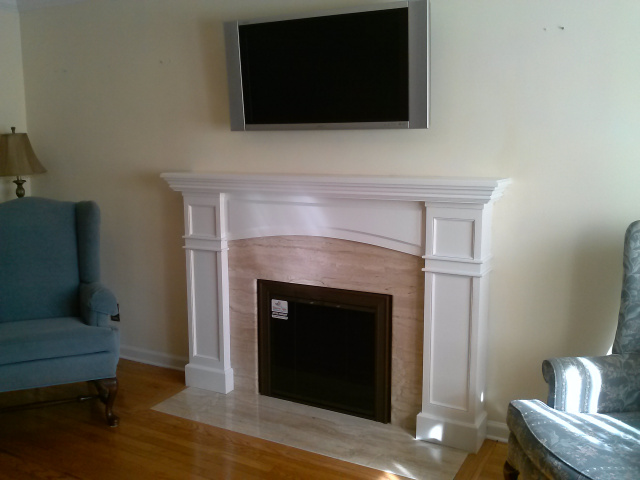 "Formalized living room fireplace with Diana Realle marble surround and hearth extention, custom arched white mantel, new 3"" oak hearth moulding and custom inside fit full swing bifold glass doors in fine textured brown with bronze glass."
