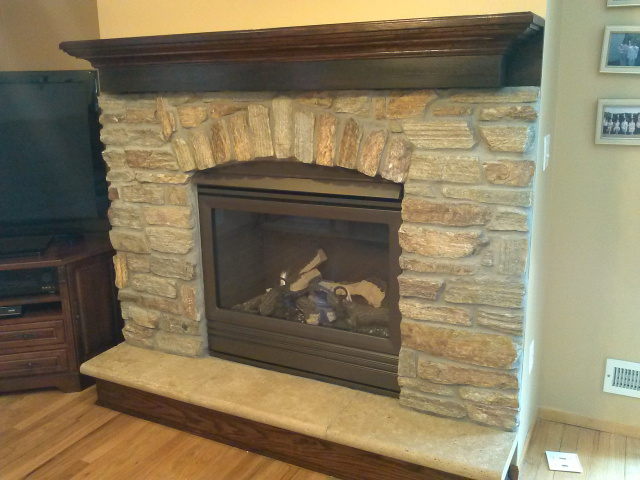 Gas Fireplace with complete new thermostatic remote controlled operating system for off the grid emergency use, goldenfire brown custom colored firebox, natural quarry stone with gentle arch, limestone hearth extention and hand rubbed red mahogany riser & mantel shelf.