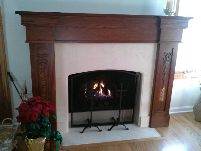 Converted to gas logs with thermostatic remote control. Limestone surround with gentle arch, custom wrought iron screen with decorative andirons and custom oak mantel in red oak finish.