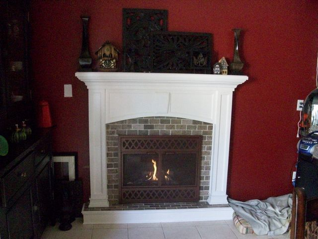 New brick tile surround, hearth step, custom mantel and custom door.